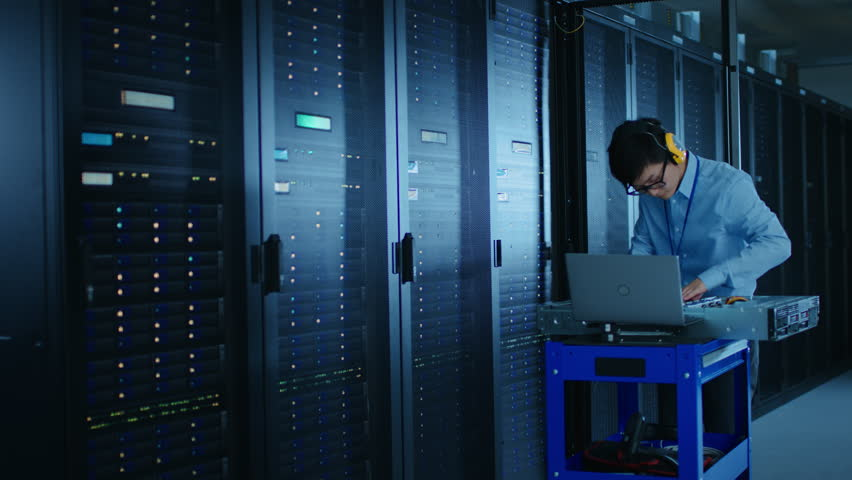 In the Modern Data Center: IT Technician Wearing Protective Headphones Working with Server Racks, on a Pushcart Installing New Hardware. Engineer Doing Maintenance and Diagnostics of the Database. | Shutterstock HD Video #1022552614