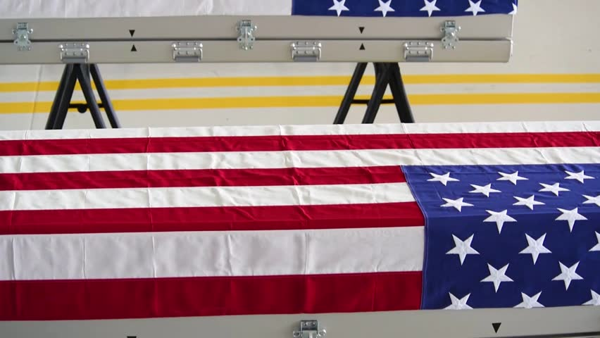 CIRCA 2018 - flag draped coffins of dead U.S. soldiers being returned home are displayed in a military hangar.