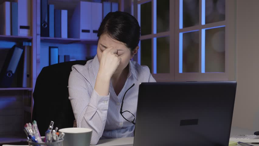 Slow motion of young woman take down glasses massage nose bridge with eyes dry overwork in office in midnight. lady worker using laptop computer suffering headache working much at night in company. | Shutterstock HD Video #1022578921