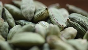 Close footage of cardamom spices in wooden bowl. Tracking shot. Selective focus.
