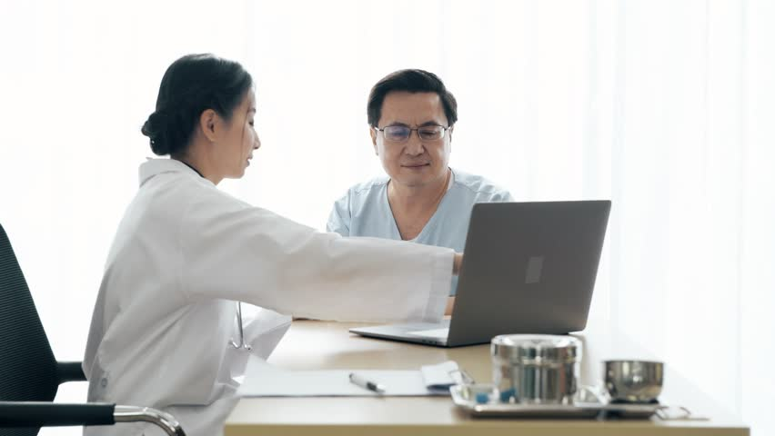 Doctor with patient. Young female medical doctor talking to a senior patient at hospital. Sharing medical test result via computer. Senior care medical and insurance concept. | Shutterstock HD Video #1022583385