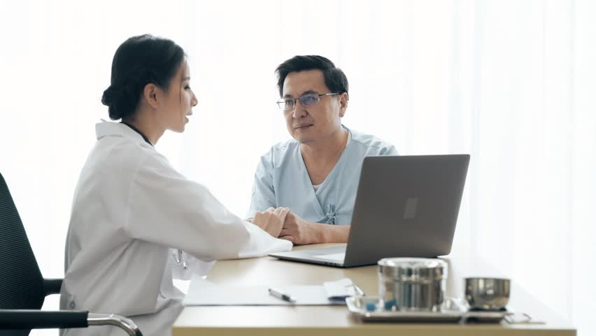 Doctor with patient. Young female medical doctor talking to a senior patient at hospital. Sharing medical test result via computer. Senior care medical and insurance concept. | Shutterstock HD Video #1022583394
