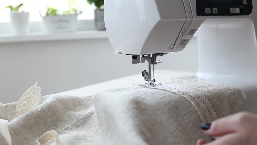 Close-up of woman's hands sewing at sewing machine at home. Automatic sewing machine. Tailor woman. Woman hobby | Shutterstock HD Video #1022589016