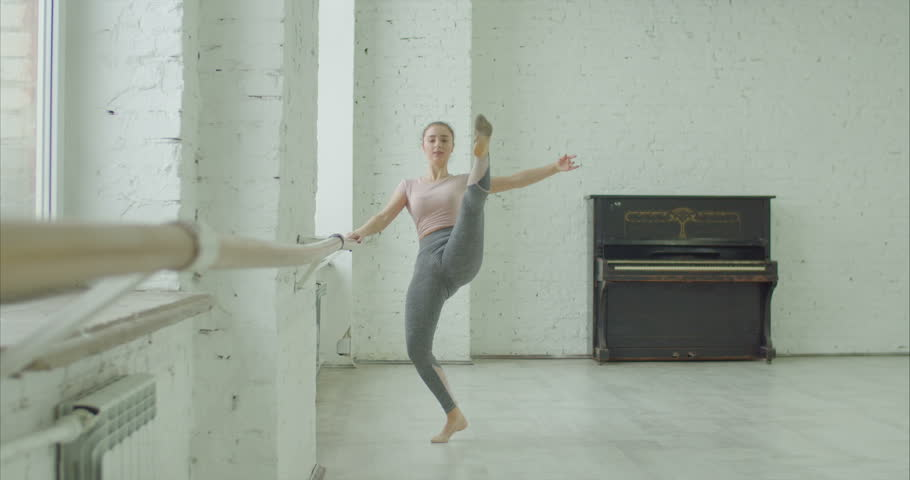 Graceful classic ballet dancer performing temps leve exersice at barre during rehearsal while training elements of classical dance in ballet studio. Ballerina practicing dance moves in dance studio | Shutterstock HD Video #1022595424