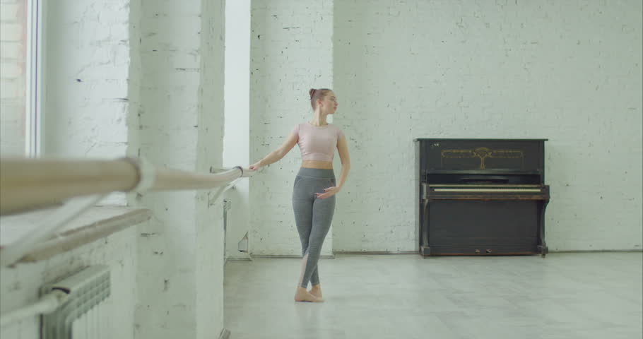 Graceful classic ballet dancer practicing picce exercise at barre during rehearsal in ballet studio. Ballerina performing different choreographic exercises and dance moves in dance studio. | Shutterstock HD Video #1022595427