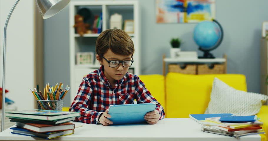 Camera zooming in of the small teen boy in glasses and plaid shirt watching something on the tablet device at the desk in the cozy kid's room.Epidemic Self isolation,Social distancing, child, kid Home