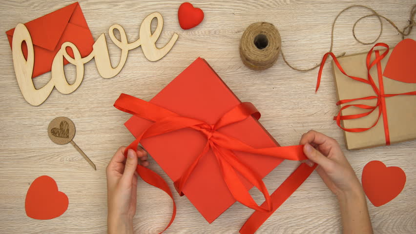 Hands unpacking Valentines giftbox with heart-shaped chocolate candies, surprise