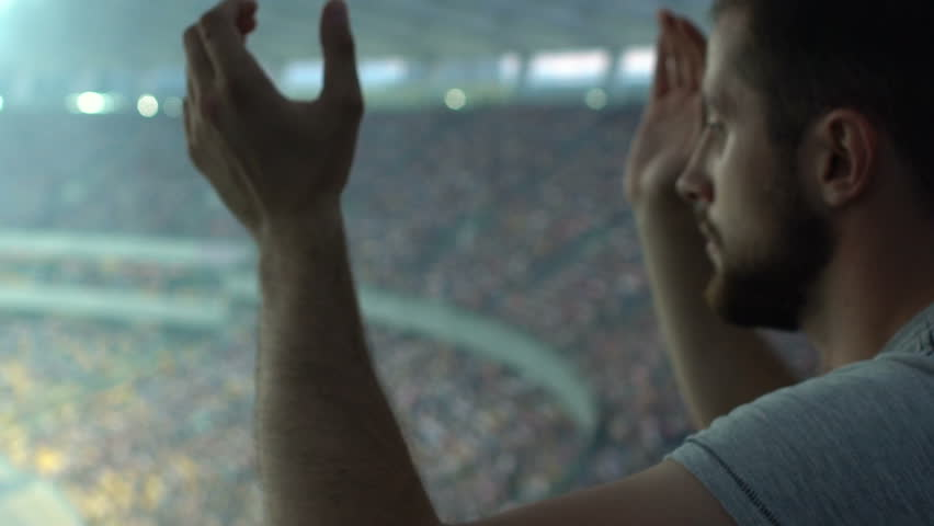 Sport fan clapping hands, watching game at stadium, supporting favorite player