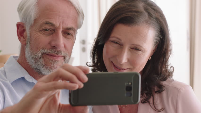 Happy middle aged couple using smartphone having video chat waving at grandchildren enjoying online communication relaxing retirement home | Shutterstock HD Video #1022614549