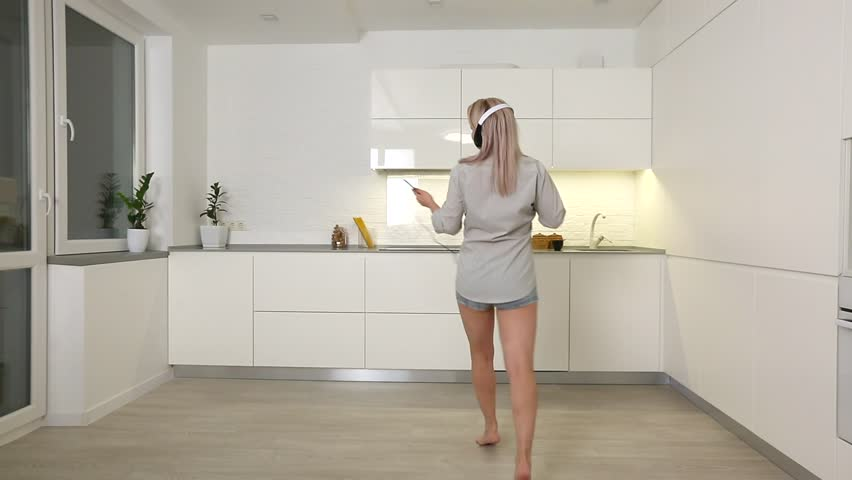 Happy young woman dancing in kitchen in the morning listening to music on smartphone #1022626477