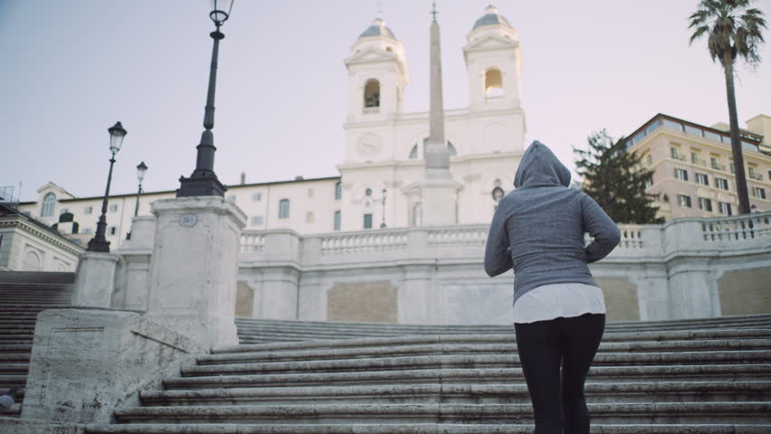 Active Italian woman running up the Spanish Steps passing a group of tourists to the top. Best fitness shot. Wide shot on 4k RED camera.