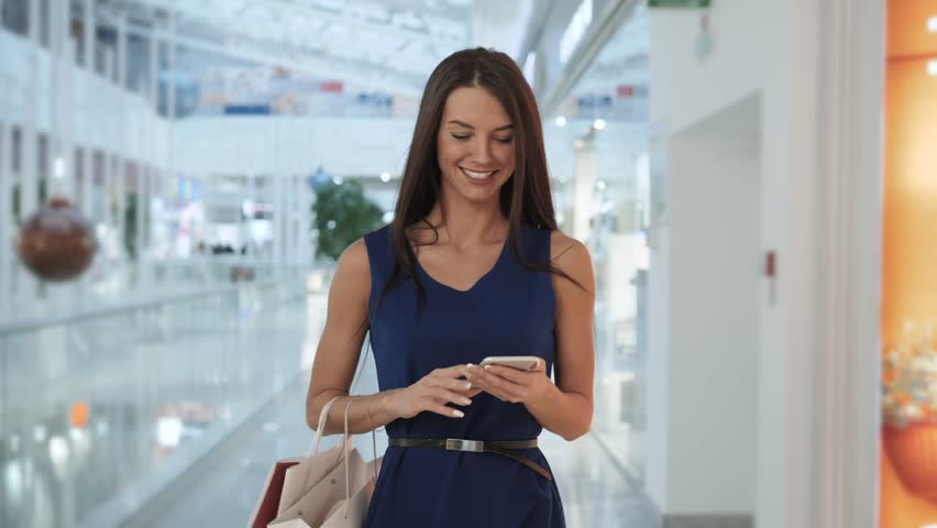 cheerful businesswoman texting on smart phone while waiting for her flight in airport terminal. shopping mall woman talk application, sexy smiling happy student tourist #1022632120
