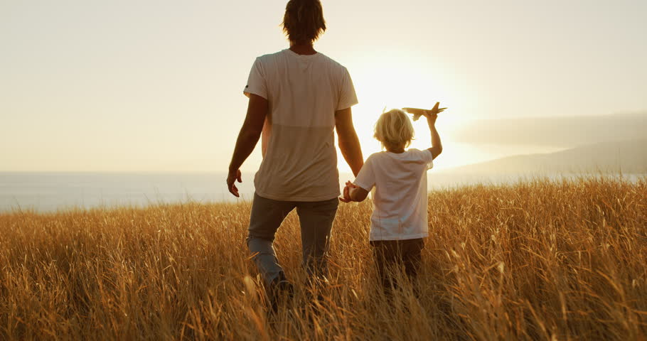 Adorable father and son walking together through golden field at sunset #1022632897