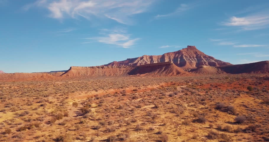 4K flying fast over the desert toward a red rock mesa revealing a mountain in the distance.