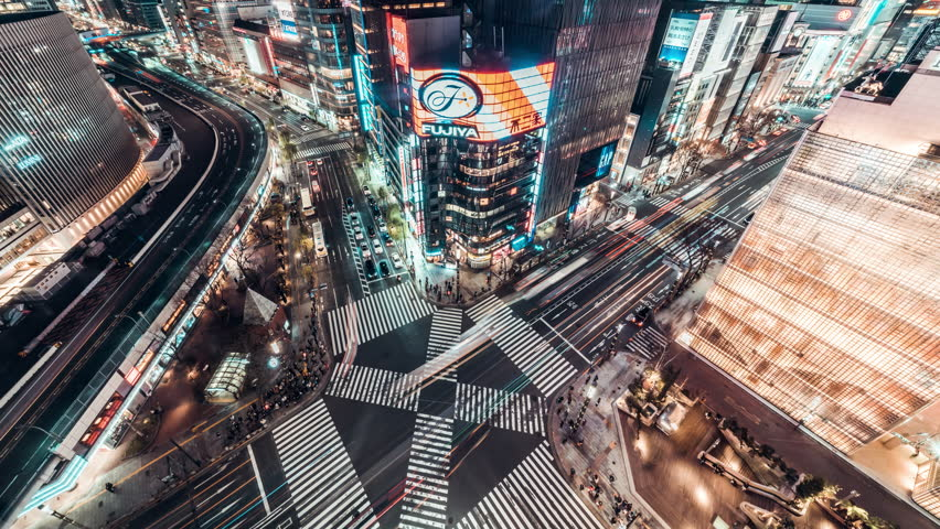 Tokyo, Japan - Jan 13, 2019: 4K UHD Aerial view time-lapse of Ginza road intersection at night, with crowded people walking on zebra crossing and car traffic light trails