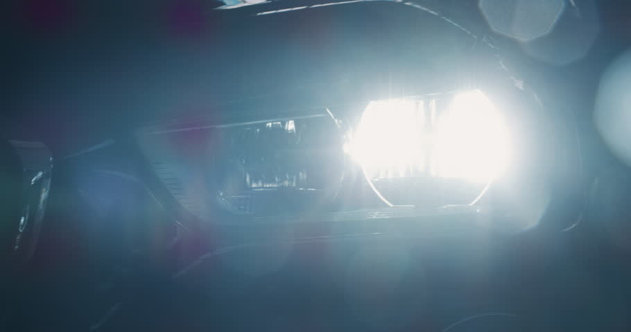 Close up of details of switched on headlights of anonymous prestigious luxury modern car. Shot in 8K. Concept of passion for driving cars and engines, car dealerships, used cars,luxury cars, auto dial
