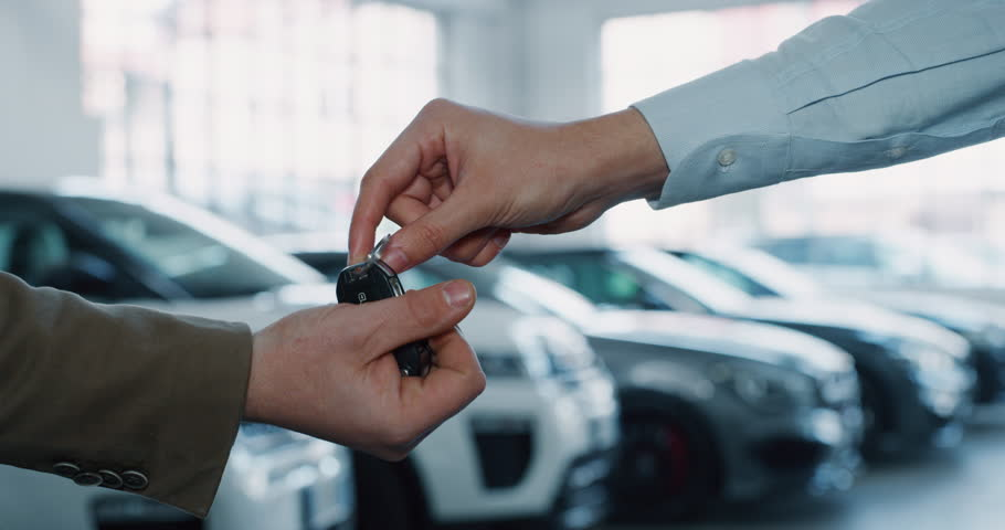 Close up of dealer giving key to new owner in auto show or salon. Slow motion shot in 8K. Concept of car dealerships, used cars, car sale and rent, auto deal