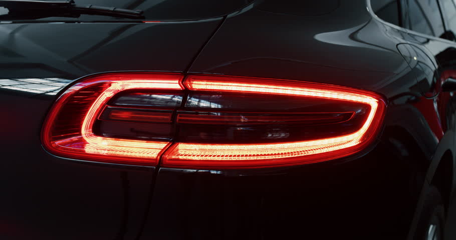 Close up of details of switched on tail lights of anonymous prestigious luxury modern car. Shot in 8K. Concept of passion for driving cars and engines, car dealerships, used cars,luxury cars,auto dial