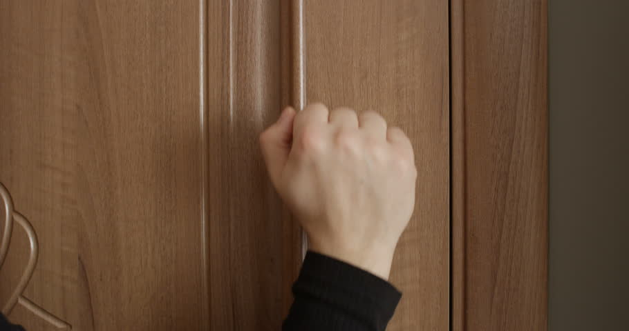 Knocking Door with Male and Female Hand Close Up Banging on the Wooden Brown Door