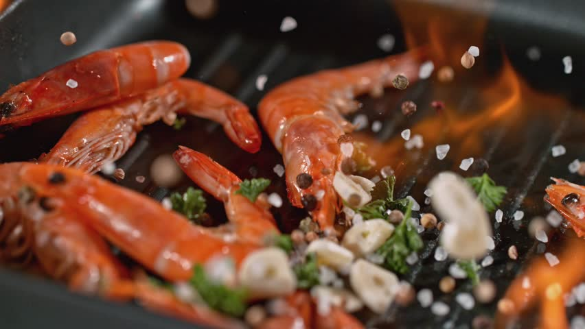 Super slowmotion footage of throwing fresh prawns and seasoning on ignited pan, 1000fps 4k