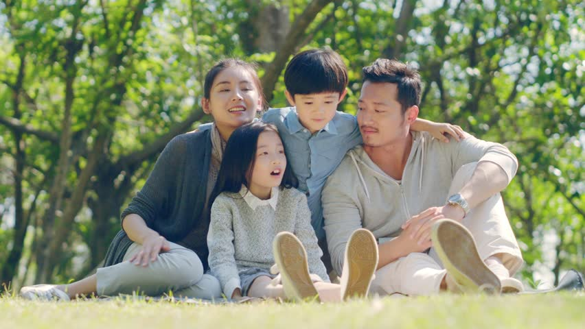 Asian family with two children sitting on grass outdoors in a park talking chatting