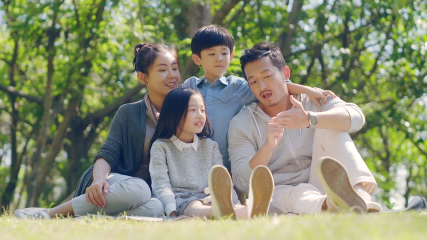 Asian family with two children sitting on grass outdoors in a park talking chatting | Shutterstock HD Video #1022674522