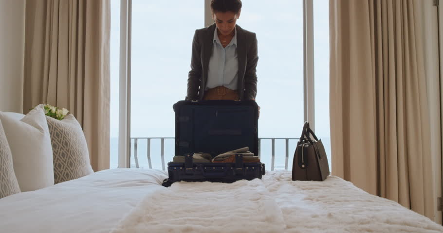 Beautiful business woman packing suitcase in hotel room getting ready for road trip preparing luggage making travel plans