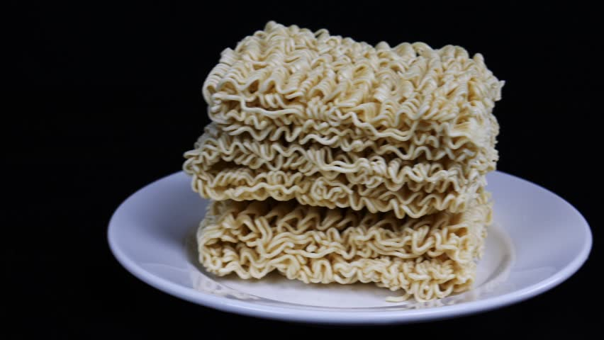 Instant noodles in a plate on a black background. Fast food, junk food, unhealthy food. Rolton. Doshirak. Close up | Shutterstock HD Video #1022690893