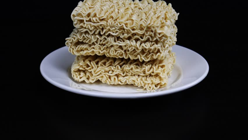 Instant noodles in a plate on a black background. Fast food, junk food, unhealthy food. Rolton. Doshirak | Shutterstock HD Video #1022690896