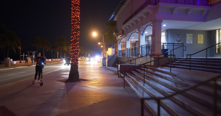 FORT LAUDERDALE, FL, USA - JANUARY 19, 2019: Fort Lauderdale Beach at night young people renting electric scooters