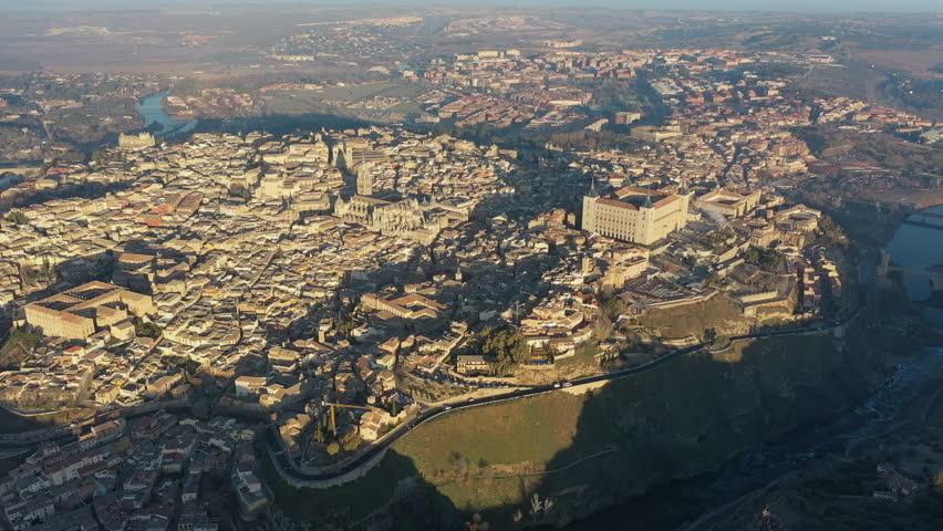 Aerial view of cityscape of Toledo at sunrise, historic center of city, castle Alcazar de Toledo and cathedral Santa Iglesia Catedral Primada de Toledo - Castilla–La Mancha from above, Spain, Europe
