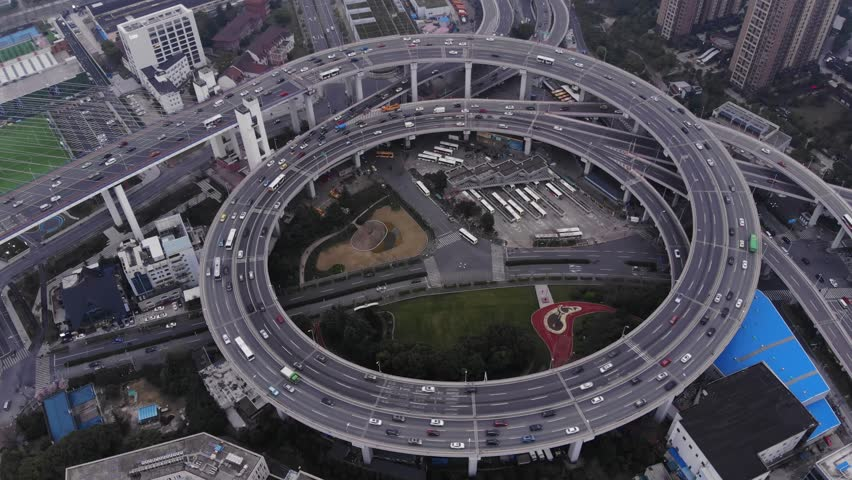 Circular junction at end of Nanpu bridge, aerial orbiting shot. Light traffic at inner ring road of Shanghai. Interesting construction of elevated interchange, large ring with slipways
