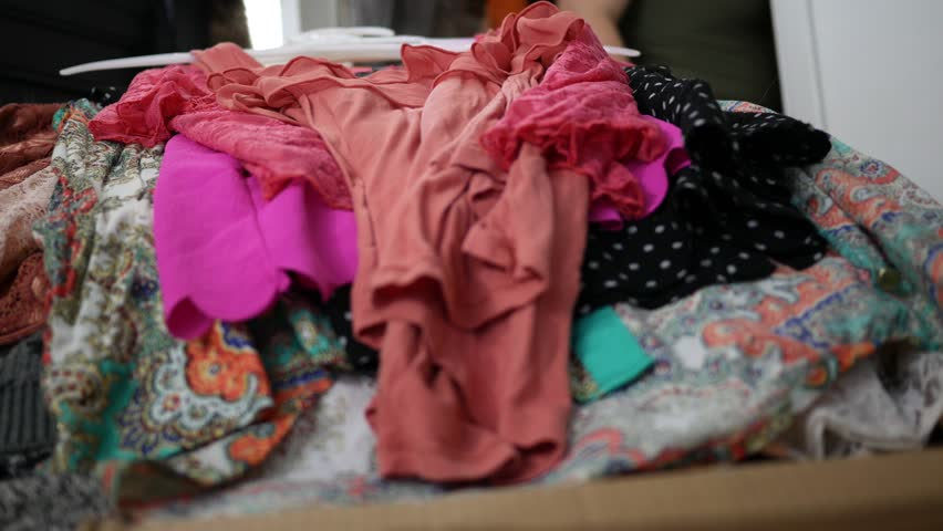 Close up of clothing piling up on bedroom bed - hoarding concept | Shutterstock HD Video #1022718676