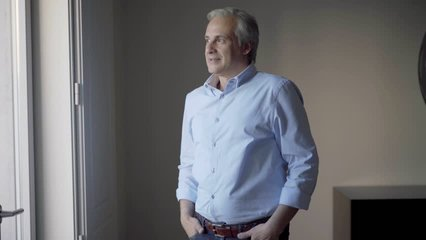 Video portrait of confident middle aged Caucasian businessman. Positive man in light blue shirt crossing arms and turning face to camera. Male portrait concept