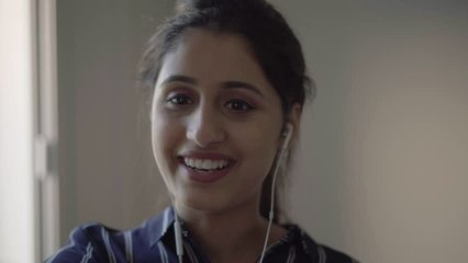 Laughing girl with earphones using smartphone for video call. Young woman talking to mobile phone screen, telling funny story or gossip. Video talk concept