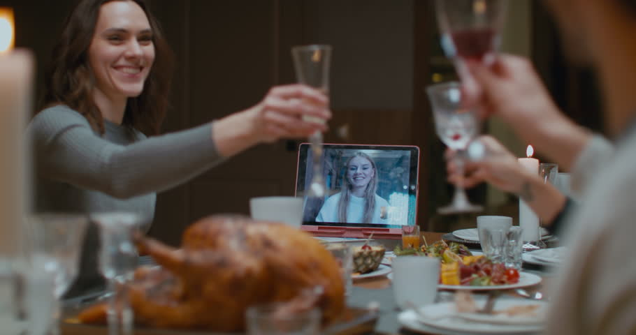 Family having a video call with relative during thanksgiving dinner, happy family greeting a remote guest. 4K UHD 60 FPS SLOW MOTION Blackmagic RAW Royalty-Free Stock Footage #1022738428