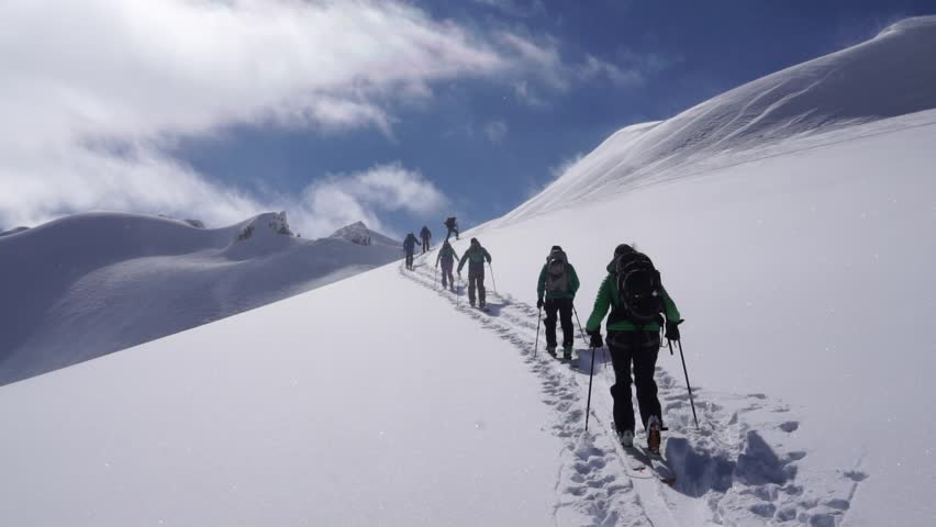 Group of backcountry skiers ascending skintrack and nearing summit   Shutterstock HD Video #1022744569