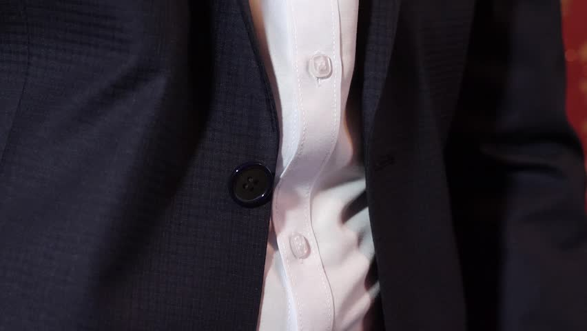 Man button up his buttons on his jacket, close-up. business man in morning puts on work.