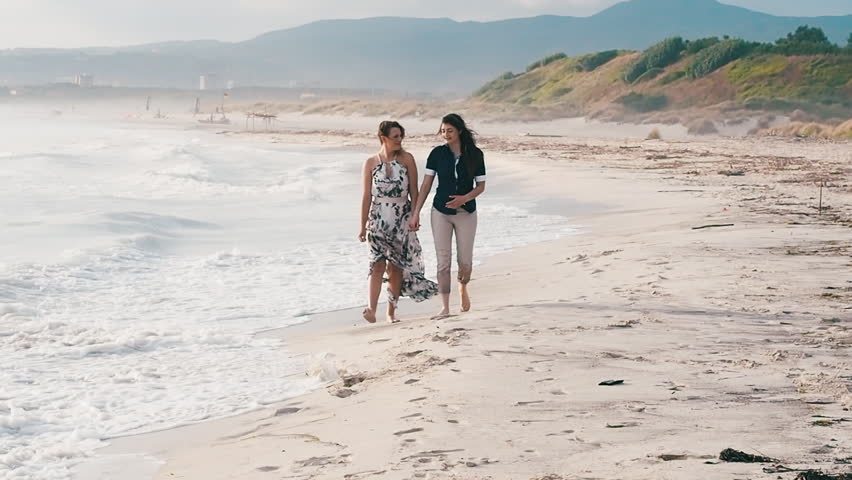 Couple of young women walking on deserted beach at sunset in summer | Shutterstock HD Video #1022758165