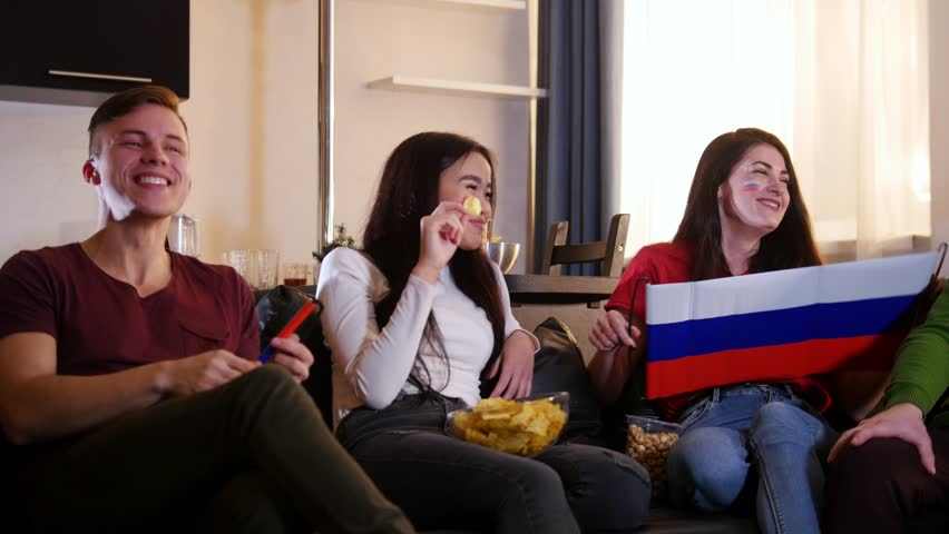 Four young happy people sitting on the sofa and watching TV together | Shutterstock HD Video #1022762920