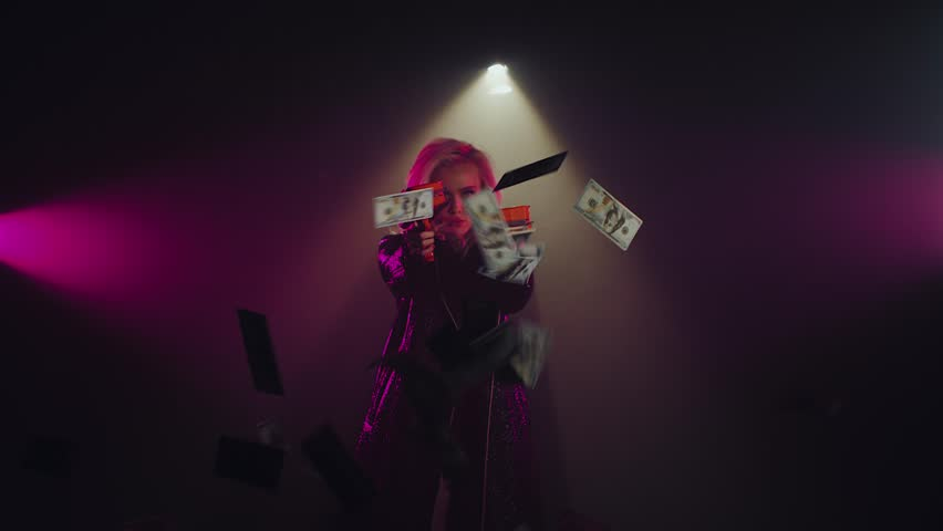 Sexual strong woman in dark long leather jacket posing with cash cannons. Edgy girl shooting lots of a money indoor. Shoot with RED RAVEN camera.