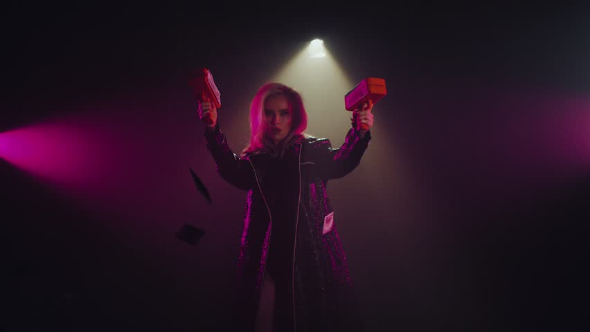 Charming cocky woman shooting two money guns in a studio room with smoke. Dollar bills flying around in a room. Shoot with RED RAVEN camera.   Shutterstock HD Video #1022772904