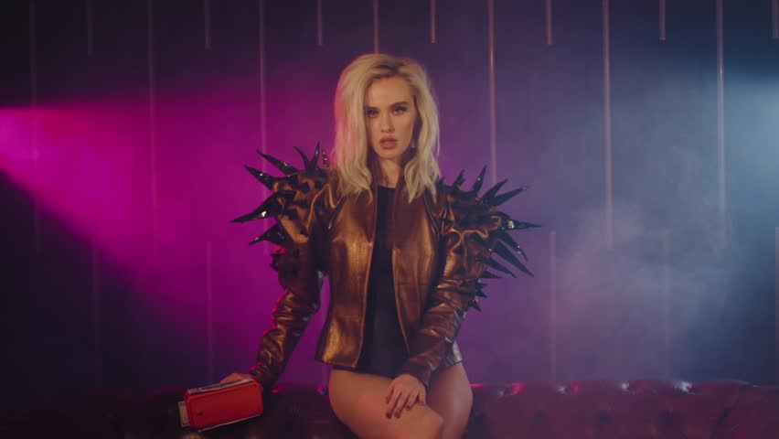 Fierce blonde rich woman sitting on a couch wearing jacket with stings and shooting money gun. Shoot with RED RAVEN camera.