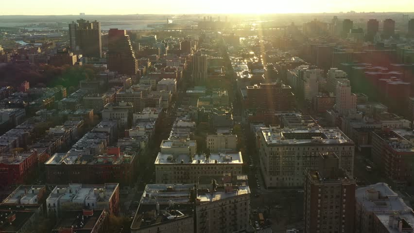 Epic golden hour sunrise drone flight over Harlem towards the sun, Manhattan, New York City. East and Harlem Rivers in the background with bridges and trains in view. in 4k.
