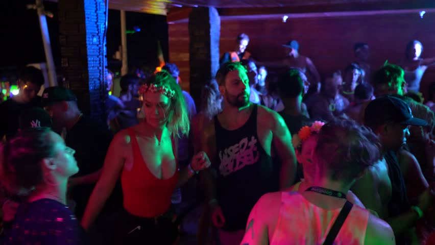 KOH PHANGAN, THAILAND - JANUARY 20, 2019 : Girls and guys participate in Full Moon party in island Koh Phangan, Thailand. Crowds people dance on the sandy beach during the full moon party. Nightlife   Shutterstock HD Video #1022780593