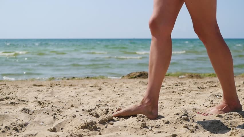 Female legs close up. The girl walks along the sea sand along the summer sunny day. #1022784721
