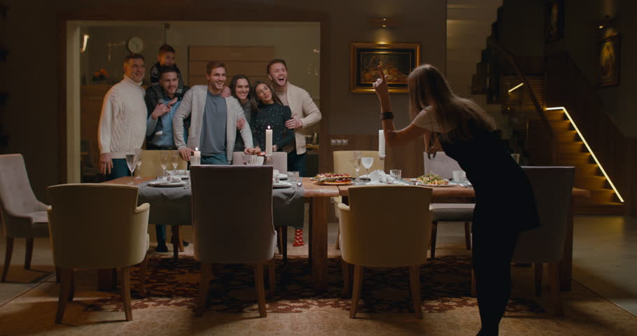 WS Large family or group of friends gather around near dining table to make a photo. 4K UHD 60 FPS SLOW MOTION Blackmagic RAW