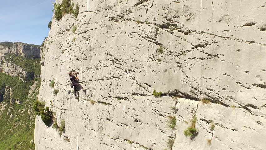 Aerial view by drone of a man climbing in free solo, without safety material, a very high cliff in Verdon, France | Shutterstock HD Video #1022819536