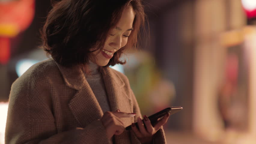 Slow motion of One pretty  young asian woman looking at mobile phone in hand smile in the city at night with blurred light at background, young people lifestyle with mobile phone in hand. 4k #1022841838