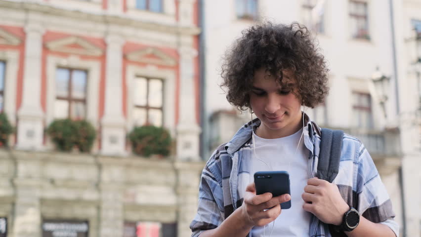 Blogger in headphones using smartphone, listening to music and browsing on smartphone. Outdoor, portrait. Man scrolls through social media on device, reading news on app #1022844907